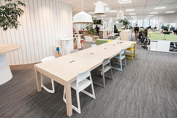 大きなテーブル席。出張者のタッチダウンスペースも兼ねており、支社からの出張者がこちらで仕事をすることが出来る。印象的なペンダントライトをつけることで、通常の執務スペースとは異なることを示すゾーニングテクニック。